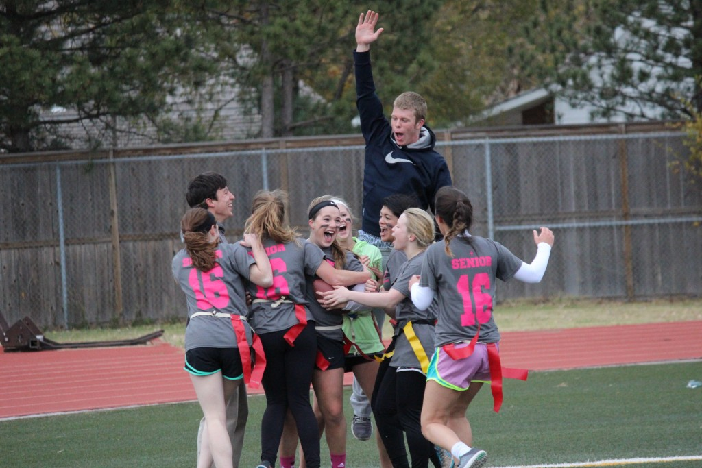 After winning Powderpuff, senior Ashley Lesser celebrates with her teammates, Sabina Kelly and Alex Castro. Coaches Brock Monty and Colter Hullings greet them as they run off the field.
