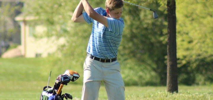 Using an iron, junior Brian Moore begins his swing at the Collegiate meet April 22. The team took fifth place with a score of 308. photo by Anna Craig