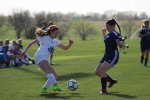 Doing a crossover move on the ball, freshman Kelsey Rae works to get around a Topeka Hayden forward April 7 against Washburn Rural at Stryker. Photo by Uyen Tran, staff photographer