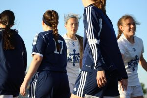 After the game against Washburn Rural April 7 at Stryker, freshman Emily Michaelis and sophomore Kaley Ball shake hands with the opposing team's members.