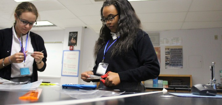 Working hard on in Biology, sophmores Nevaeh Sanchez and Jackie Gifford concentrate on cutting out hares and lynx for an assignment  on Sept. 9.