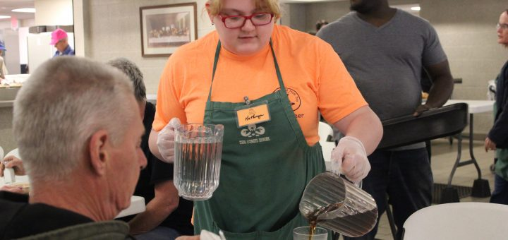 Senior Katherine Ludlam is a refiller and she is giving the man tea at Lord's Diner  March 27. photo by Sarah Nguyen, staff photo editor