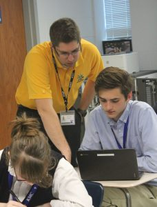 In first block geometry, math teacher Ray Luman assists sophomore Eli Herlocker with ACT prep on the computers April 20.