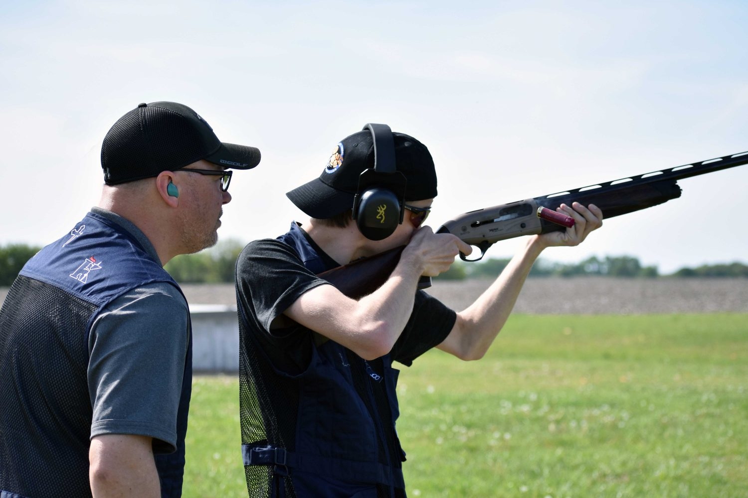 Trap+shooting+team+coach+Chris+Harter+watches+on+as+shooter+Jordan+Ehrke+points+his+shotgun+during+practice+at+Ark+Valley+Gun+Club+April+23.