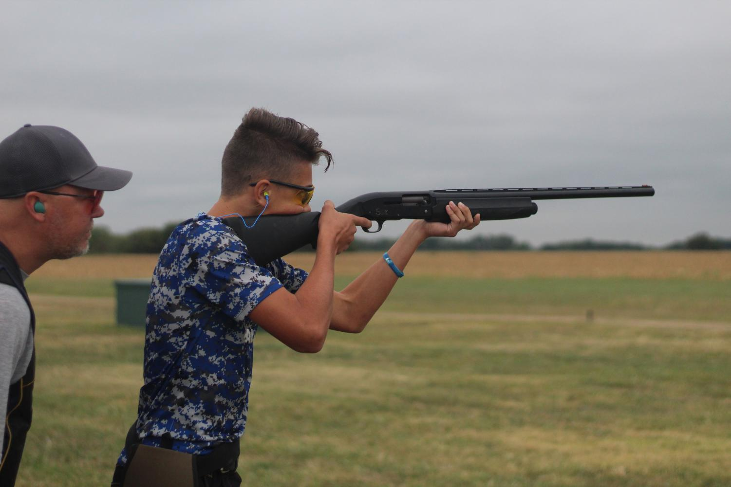 During his first week of competition at Ark Valley Gun Club on the KMC Trapshooting team, Freshman Jacob Steffen, with the help of coach Chris Harter, prepares for his next shot. Overall Jacob was one of the most improved shooters on the team . Photo by Jared Welsby, Staff Photographer.