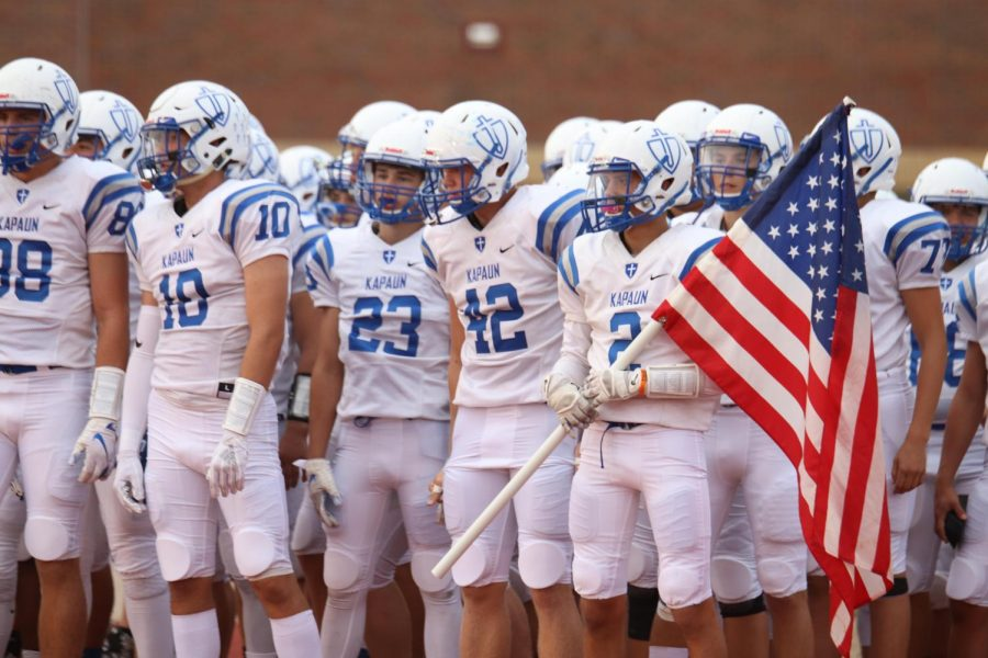 Senior Jacob Nye holds the American flag as the Crusaders prepare to take the field at Andover District Stadium Sept. 21.