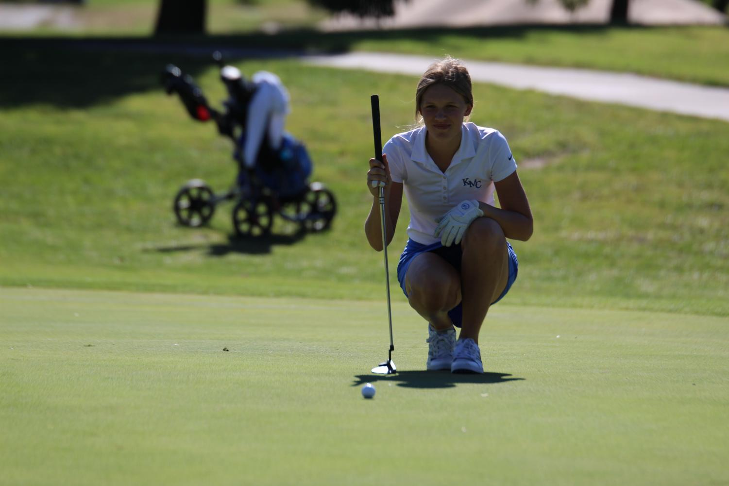 Reading the slope, Junior Lauren Rudy squats down to make a decision on how to putt at the girls golf tournament Sept. 26 at the Arthur B. Sim public golf course