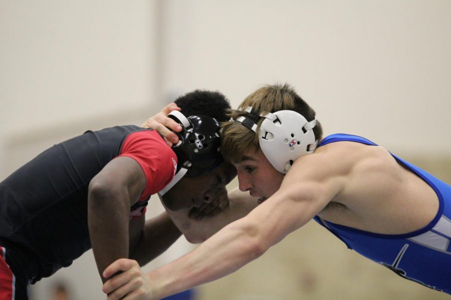 Grabbing his opponent, senior Logan Jiminez battles a wrestler from Heights Dec. 6 in the KMC gym. The wrestling team beat Heights 76-6 in their second dual of the regular season. The team's first dual was a 58-15 win at South Dec. 1. photo by John Biehler