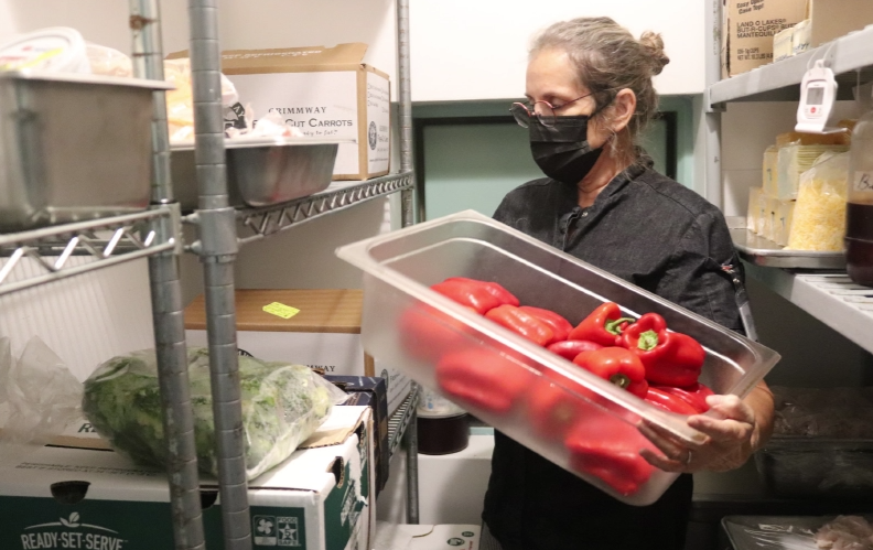 Arranging food for the day, Cafeteria Manager and Chef Denise Unruh takes peppers out of the freezer closet Wednesday, Sept. 23. She will use them for future meals. photo by Diana Pham