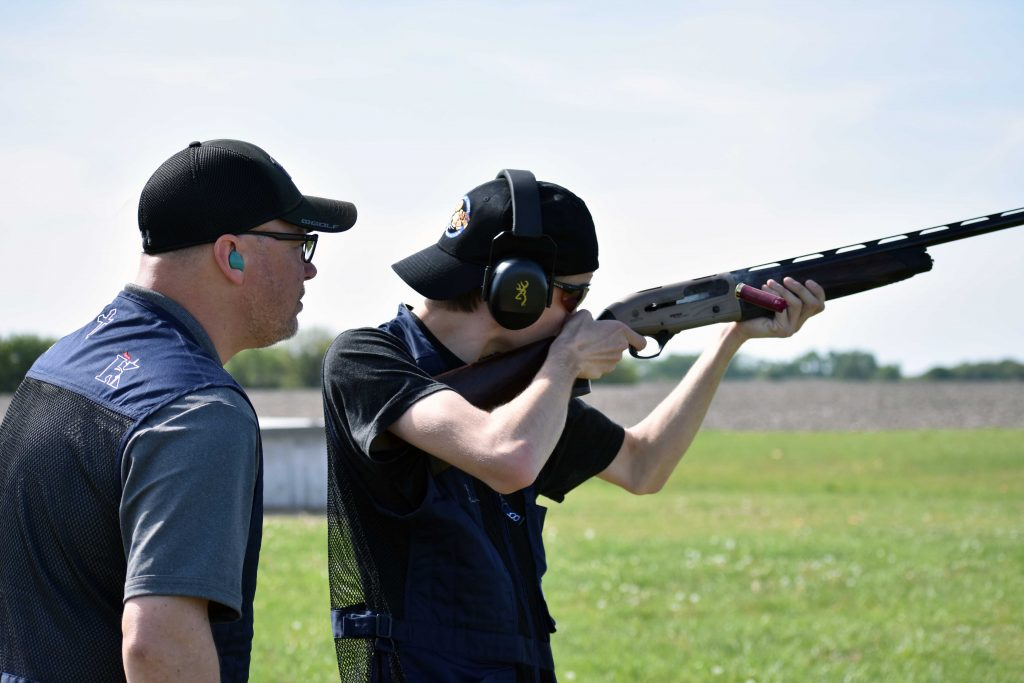 Trap shooting team coach Chris Harter watches on as shooter Jordan Ehrke points his shotgun during practice at Ark Valley Gun Club April 23.