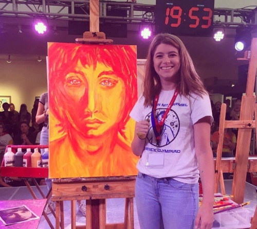 Posing in front of her second painting, senior Aubrey Pennington pauses for a photo at the Mark Arts Versus Student Art Battle held at Mark Arts Sept. 22. For a video of Pennington painting visit kmccrusade.com photo courtesy of Lori Sprague