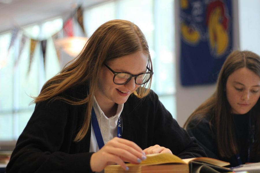 Kapaun Mt. Carmel juniors Maddie Robinson and Isabel Ultzsch work in the library on Sept. 9, wearing clothes from Parker School Uniforms. The closing of Parker has left the future of Diocesan school uniforms in limbo. Photo by Haley Cahill.
