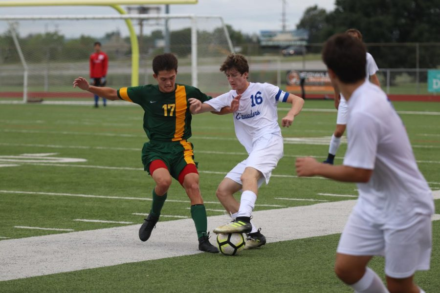 Fighting for the ball, junior Patrick Dehner battles a Bishop Carroll defender at South during the semifinals of the Titan Classic Sept. 6. The Crusaders lost 1-0. South's field is serving as the team's home this season.