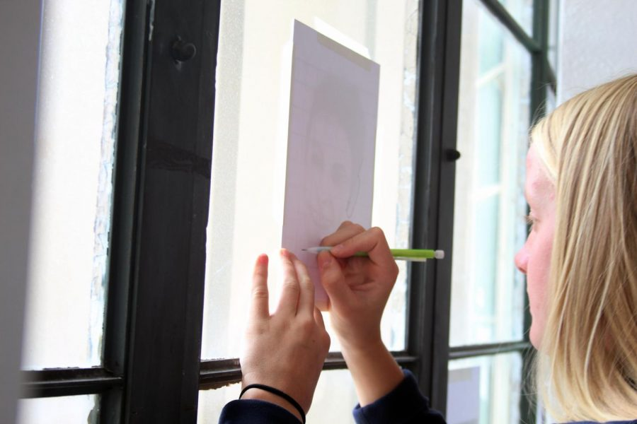 Using the sunlight, sophomore Ali Nye traces a picture of Chace Crawford outside of the art room Sept. 24 in block 7. The class was using this technique to learn how to shade faces.