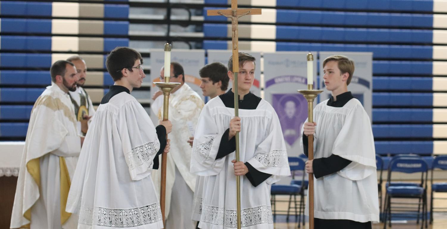 Processing out of Mass, sophomore Nick Wetta carries the cross while junior Daniel Samsel (left) and sophomore Tim Post (right) hold the candles Sept. 12 in the gym. Mass was celebrated by vocations director Fr. Chad Arnold. Afterwards, the Homecoming court candidates were presented to the school. photo by John Biehler
