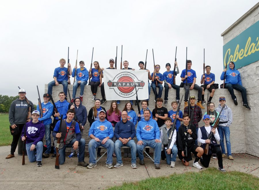 Before practice Oct. 7,  the trapshooting team poses with their shotguns for a team photo. Finishing up its fourth season, the team is currently in third place in its league. See at kmccrusade.com for video footage. photo courtesy of John Biehler