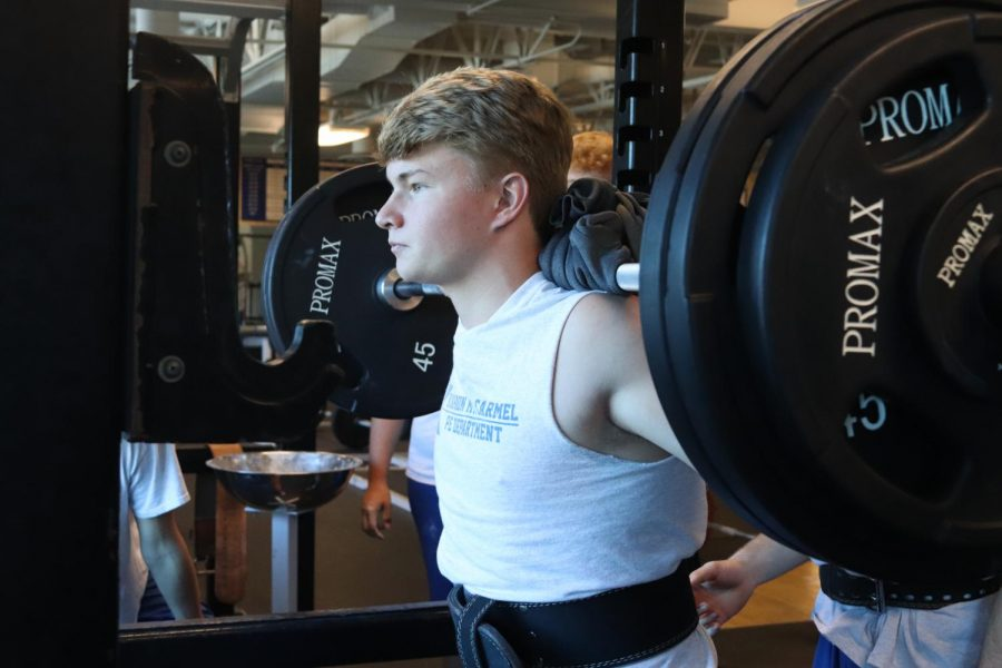 Positioning himself in the squat rack, sophomore Reece Eberhart prepares to squat in his second block weights class with coach Dan Adelhardt. Attending weights class in one way to earn more points, which are to encourage athletes to do off-season work. For a video about weights class, see our instagram account @kmccrusade.