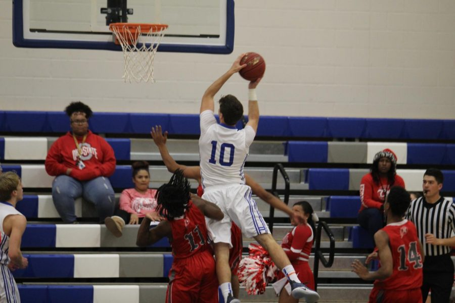 Going up for a basket, senior Scott Valentas jumps to earn a point. The Crusaders won their game against North on Dec 8.