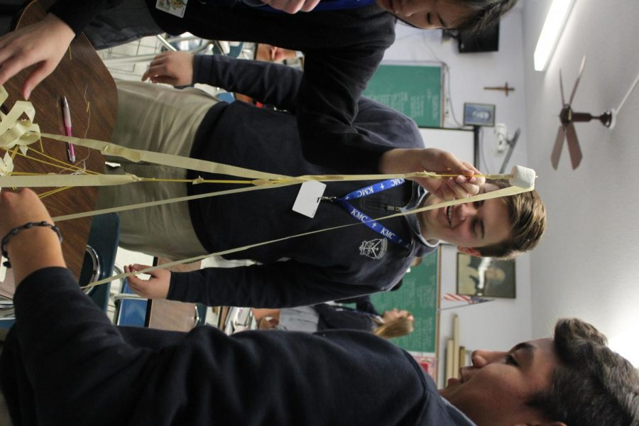 Adjusting their tape and raw spaghetti noodles, sophomores Sharlene Tran and Joseph Sanchez and freshman Jackson Engle construct a tower for the HOTY competition during CAP time Jan. 8. The tallest tower belonged to Ignatious of Loyola at 36 inches. photo by Isabella Perez