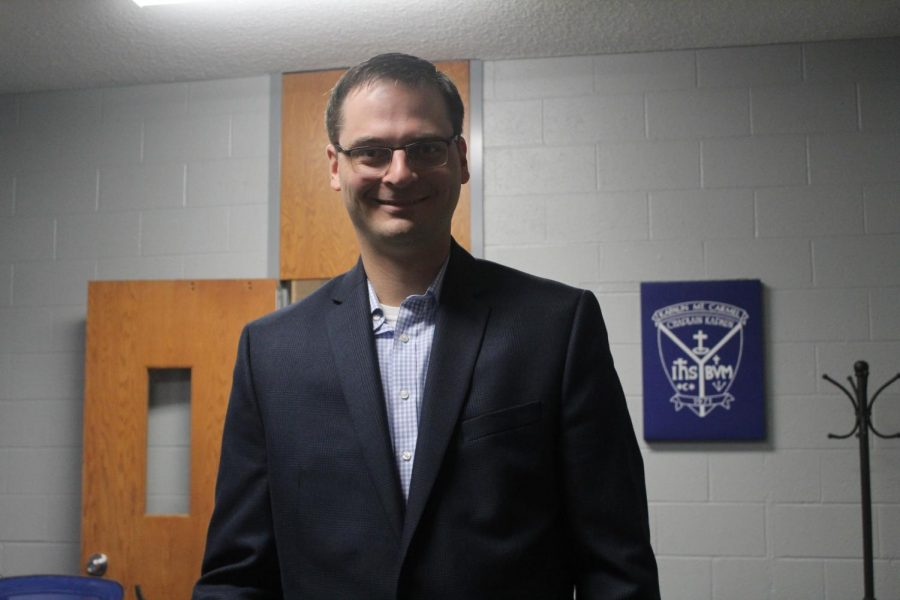 In the faculty lounge, future Dean of Academics David Stephenson poses for a photo after meeting the faculty and teachers at Kapaun Mt. Carmel  and touring the building Jan. 18. He will start the role July 1. photo by Krystal Luong