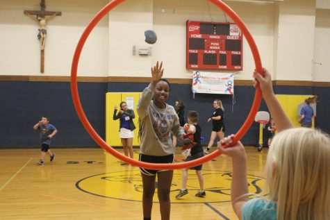 Throwing a bean bag, senior Natalie Oduor plays bean bag toss with one of the children at St. Joseph Elementary. Oduor volunteered at Little Athletes with National Honor Society April 24. photo by Maggi Duncan