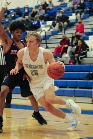 Senior Grant Johnson dribbles past his opponent aggressively. The boys won 56-46 against Heights. KMC played Heights Jan. 26 at KMC.