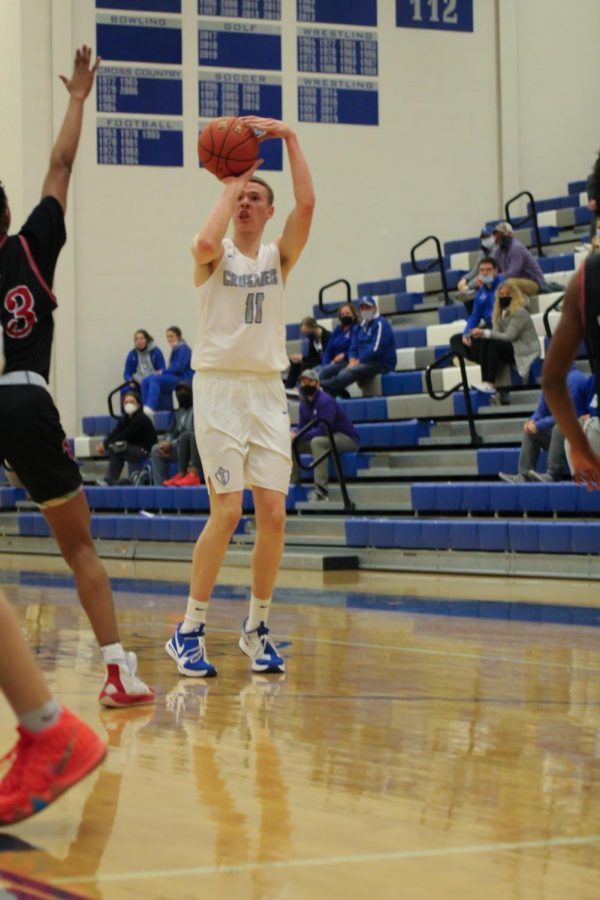 Henry Thengvall looks to shoot for a 3-point shot. KMC played against Heights on Jan 26. at KMC. The boys beat the Falcons 56-46.
